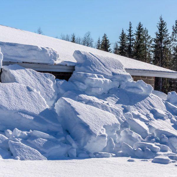 Valtava lumimäärä on tippunut ulkorakennuksen katolta.