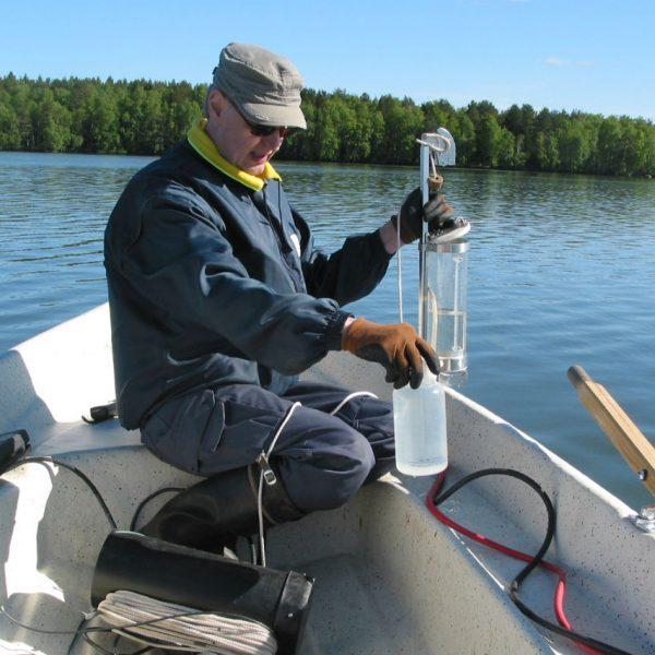 Vesinäytteen ottaja veneellä järvellä.