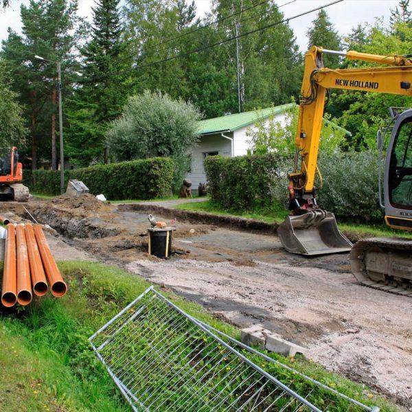 Kaivuri kaivaa omakotitalon vesiputkea maahan.