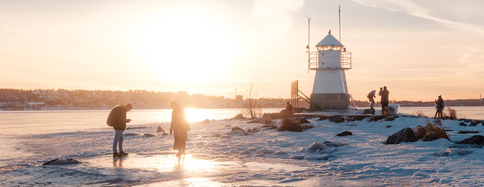 Ihmiset ulkoilevat kevätjäällä Siilinkarin majakan edustalla Tampereen Pyhäjärvellä