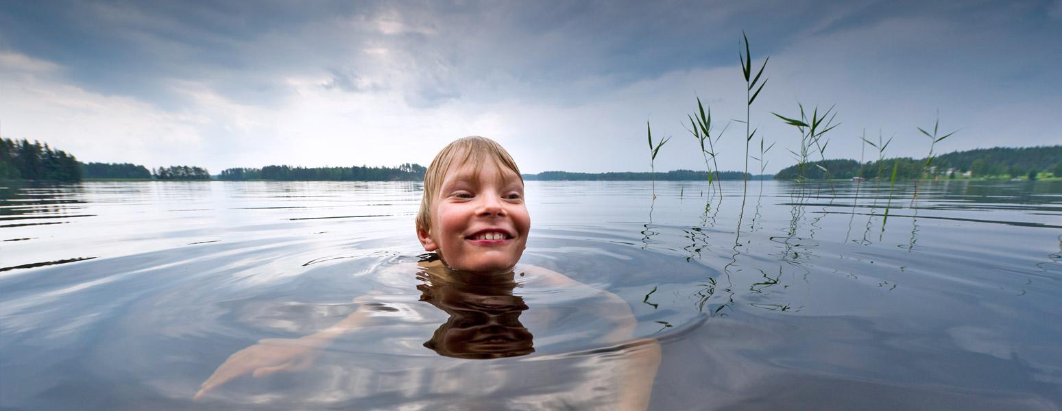 Nuori iloinen poika ui järvessä.